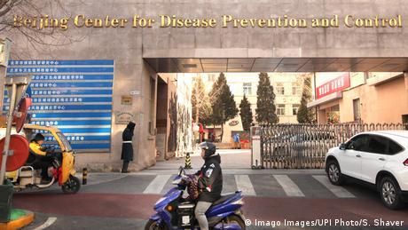 Una persona pasa con un scooter frente a un centro de salud y prevención en Beijing.