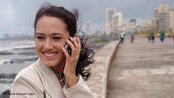 A young Indian businesswoman on a mobile telephone on a wharf