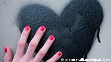 ARCHIV- ILLUSTRATION - Eine Frauenhand mit rot lackierten Fingernägeln berührt am 03.03.2014 in Berlin ein Herz, das auf eine Mauer gesprüht wurde. Foto: Inga Kjer/dpa (zu dpa Herzinfarkt ist nicht nur Männersache - Das Frauenherz tickt anders) +++(c) dpa - Bildfunk+++ | Verwendung weltweit