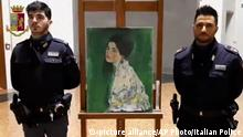 """This image taken from a video distributed Wednesday, Dec. 11, 2019 by Italian police shows two police officers standing next to painting which was found inside a gallery's walls, in Piacenza, northern Italy. A gardener at the Ricci Oddi modern art gallery in the northern city of Piacenza told Italian state TV on Tuesday that he was clearing ivy from the gallery's walls when he noticed a metal panel in which he found a bag inside a space within the walls. When the bag was opened it contained a painting that might be Klimt's """"Portrait of a Lady,"""" which disappeared from the gallery during renovations in February 1997. (Italian Police via AP) 