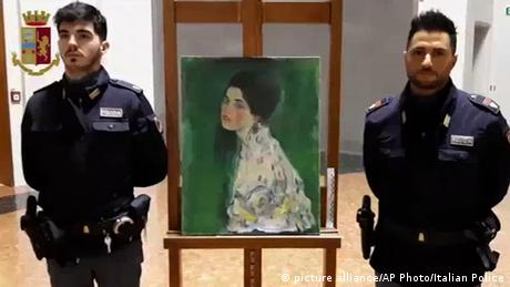 Two police officers stand next to a Klimt painting that was missing for 23 years. (picture alliance/AP Photo/Italian Police)