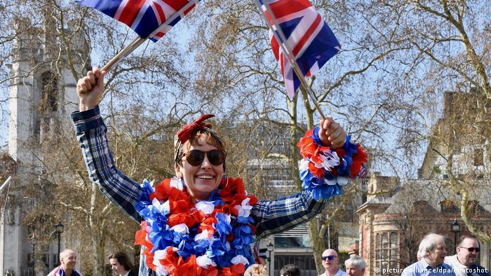 A brexiteer waves union jack flags wearing sunglasses