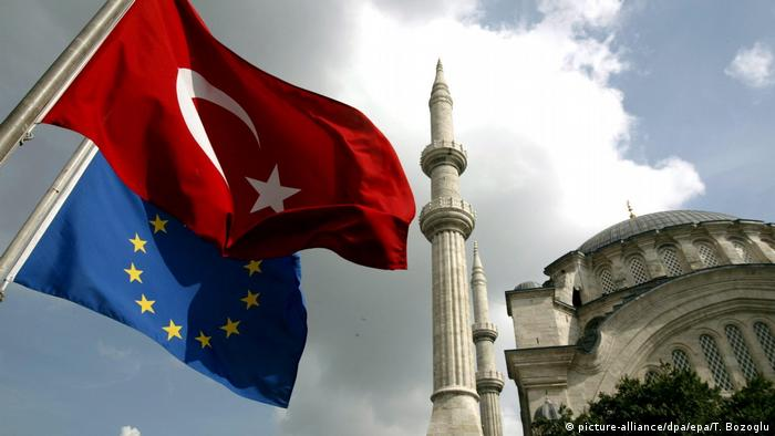 A Turkish and EU flag wave in front of a historic mosque