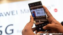 A Huawei smartphone taking a picture of billboard advertising 5G services (picture-alliance/Photoshot)