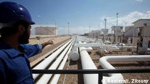 FILE PHOTO: A worker gestures towards pipelines at the port and Zawiya Oil Refinery, Aug. 22, 2013. REUTERS/Ismail Zitouny/File Photo