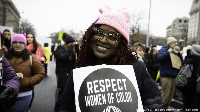 A woman holds a sign that reads, Respect women of color