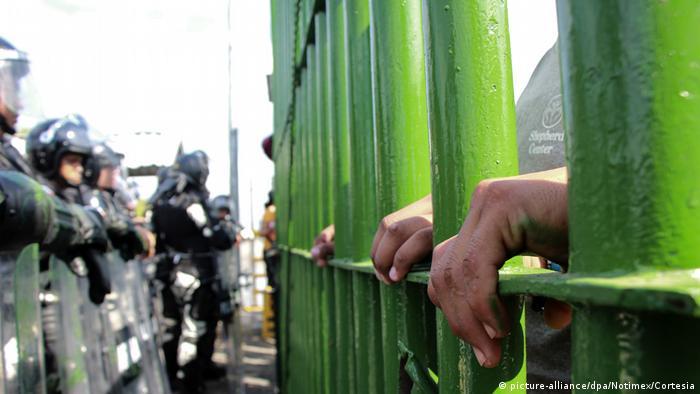 Migrantes detrás del muro fronterizo entre México y Guatemala, frente a policías armados.