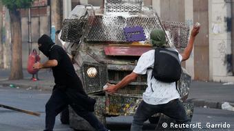 Foto de manifestantes enfrentándose a la policía.