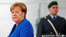 German Chancellor Angela Merkel waits to welcome Republic of the Congo's President Denis Sassou Nguesso at the beginning of the Libya summit in Berlin, Germany, January 19, 2020. REUTERS/Hannibal Hanschke