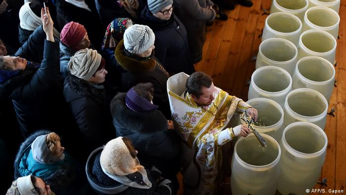 A priest blesses barrels of holy water (AFP/S. Gapon)