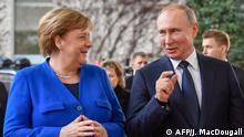 German Chancellor Angela Merkel greets Russian President Vladimir Putin (C) with Secretary-General of the United Nations (UN) Antonio Guterres upon his arrival to attend the Peace summit on Libya at the Chancellery in Berlin on January 19, 2020. - World leaders gather in Berlin on January 19, 2020 to make a fresh push for peace in Libya, in a desperate bid to stop the conflict-wracked nation from turning into a second Syria. Chancellor Angela Merkel will be joined by the presidents of Russia, Turkey and France and other world leaders for talks held under the auspices of the United Nations. (Photo by John MACDOUGALL / AFP) / ALTERNATIVE CROP