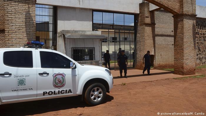 Carro de polícia e policiais diante de entrada de presídio