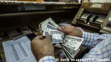 A man counts Egyptian pounds at currency exchange shop in downtown Cairo on November 3, 2016. Egypt floated the country's pound as part of a raft of reforms, after a dollar crunch and exorbitant black market trade threatened to grind some imports to a halt. / AFP / KHALED DESOUKI (Photo credit should read KHALED DESOUKI/AFP via Getty Images)