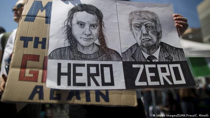 A woman holds a placard depicting Swedish activist Greta Thunberg and US President Donald Trump at a climate rally