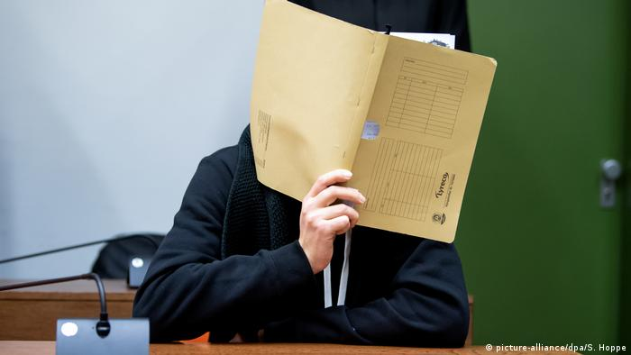 A man accused of impersonating a doctor online to get women to electrically shock themselves sits in court in Munich, Germany