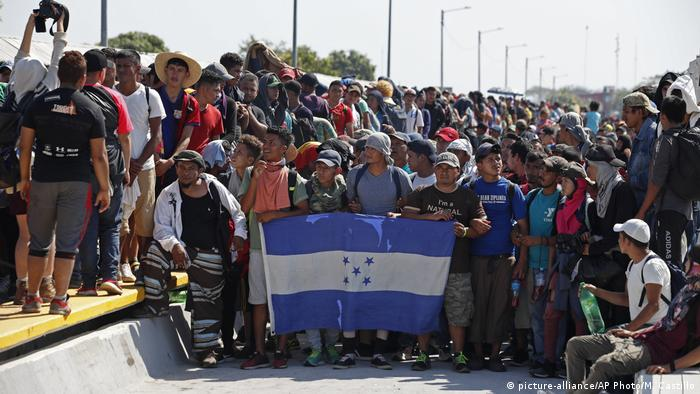 Central American migrants holding Honduras' national flag stand on the legal border crossing bridge over the Suchiate River (picture-alliance/AP Photo/M. Castillo)