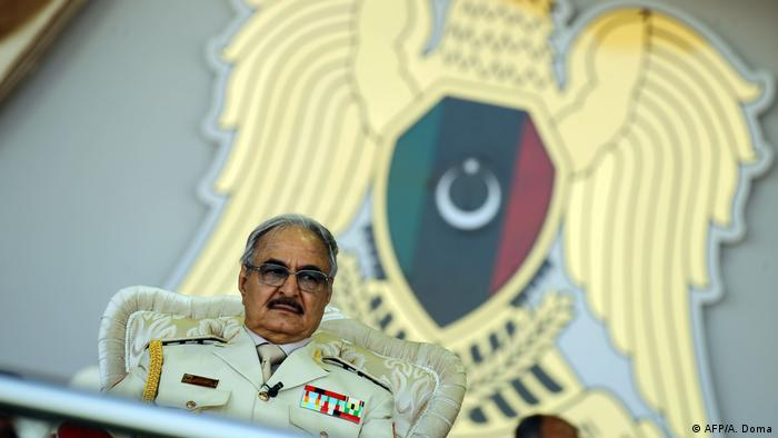Libyan strongman Khalifa Haftar sits in military uniform in front of an eagle emblem featuring the Libyan flag.