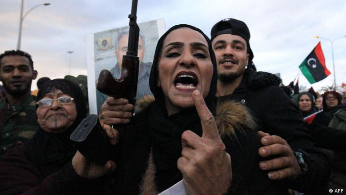 A Libyan female protestor points to the camera while a man stands behind her with a gun