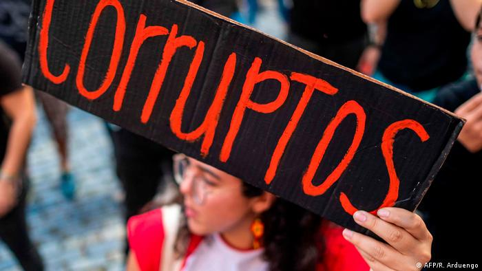A person holding a sign reading 'corruptos' Protest (AFP/R. Arduengo)