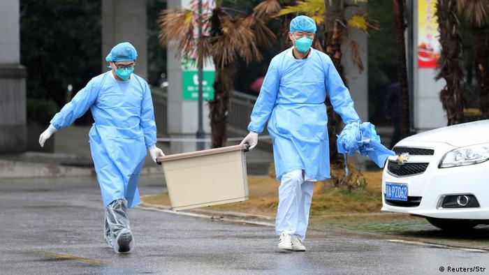 Personas con ropas especiales y mascarillas llevan una caja con material médico en Wuhan.