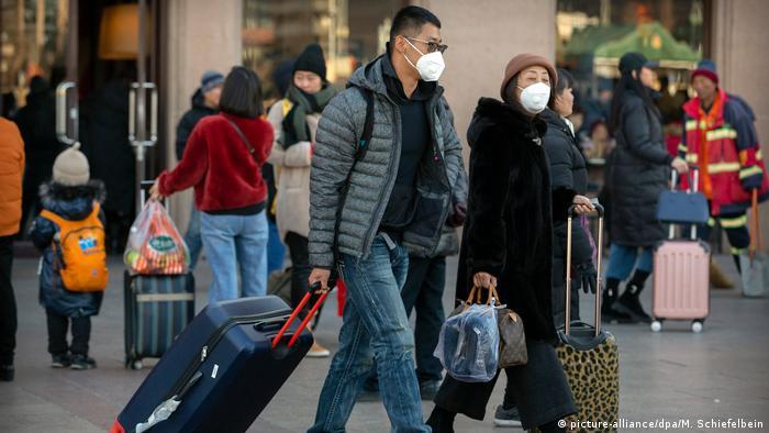 Пассажиры в медицинских масках с чемоданами на вокзале в Пекине