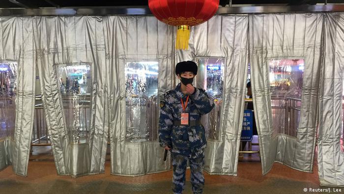 Tanto el personal de seguridad, como el de la Estación Oeste de Beijing, utilizan máscaras de respiración para protegerse de la infección. Las lonas de plástico sirven como protección contra el frío.