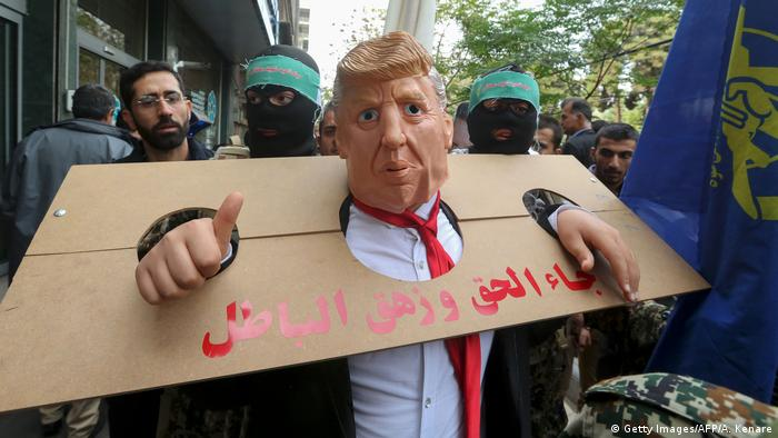 An Iranian protester dressed as US president Donald Trump in a pillory
