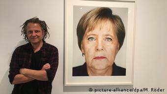 Фотограф рядом с портретом Ангелы Меркель