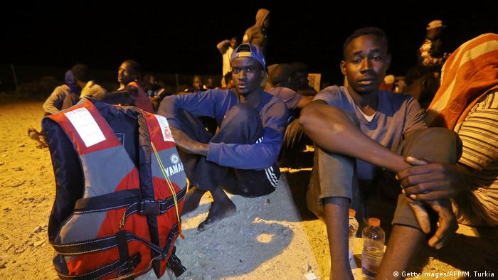 Rescued African migrants sit on Libyan coast after being rescued from the Mediterranean Sea.