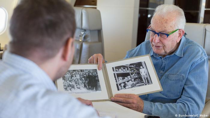 Naftali Fürst holds up a photo taken of him at a concentration camp