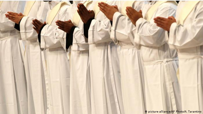 Priests pray during a ceremony in St. Peter's Basilica at the Vatican