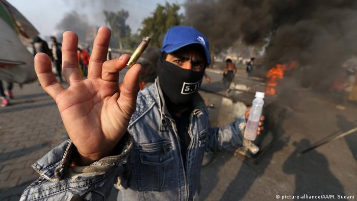 Протестующий в Багдаде показывает пулю