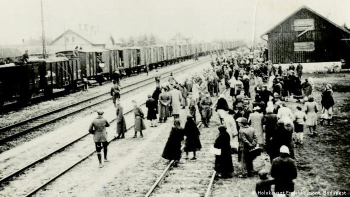 Photo of people standing beside railroad tracks in 1944, guarded by SS members (Holokauszt Emlékközpont, Budapest )