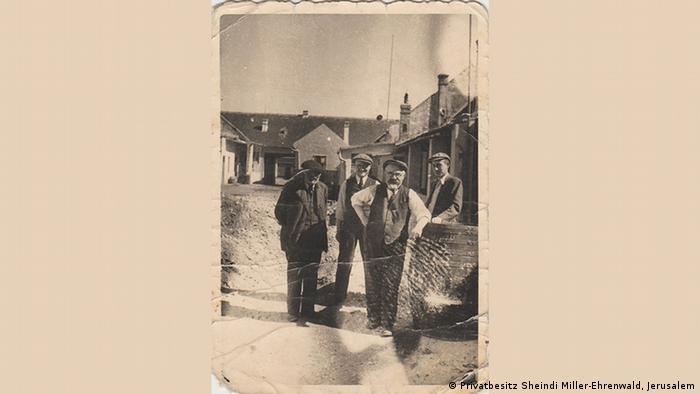 Uma foto histórica mostra quatro homens parados junto a uma cerca