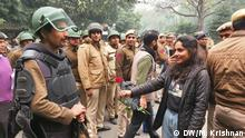 A female protester holds a flower at a soldier during an protest in New Delhi