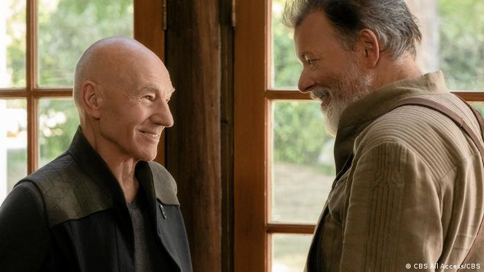 Serie Star Trek: Picard, Szenenbild: Jean Luc Picard (Patrick Stewart) und Commander Riker (Jonathan Frakes) sehen sich nach vielen Jahren wieder und stehen sich freundlich lächelnd gegenüber