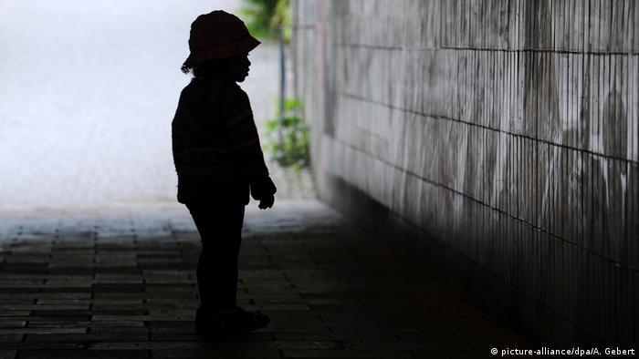 Silhouette of a child in front of a wall