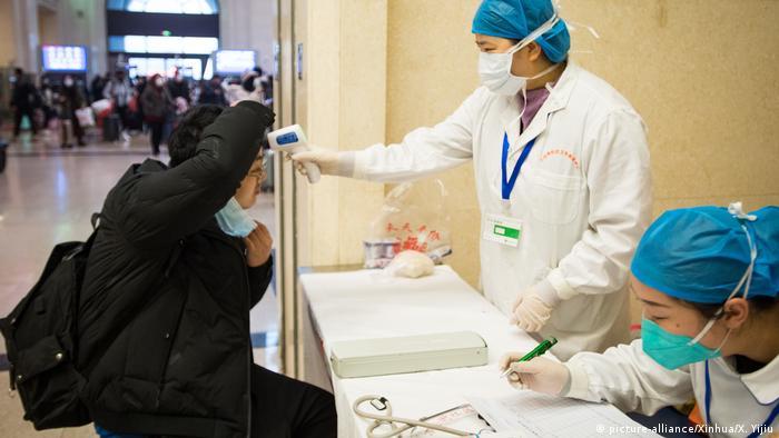 Medicinski radnik kontrolira tjelesnu temperatutu prolaznika na željezničko stanici u Hankou