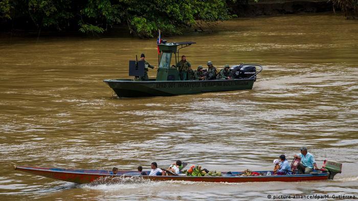 Foto simbólica de militares venezolanos en una embarcación que miran a personas de otra lancha en un río.