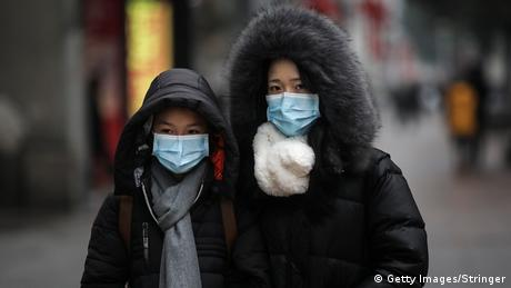 A family wears masks while walking in the street on January 22, 2020 in Wuhan, Hubei province, China. (Getty Images/Stringer)