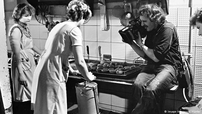Two women hunched over an oven with bread loaves on it, a cameraman filming them closeup