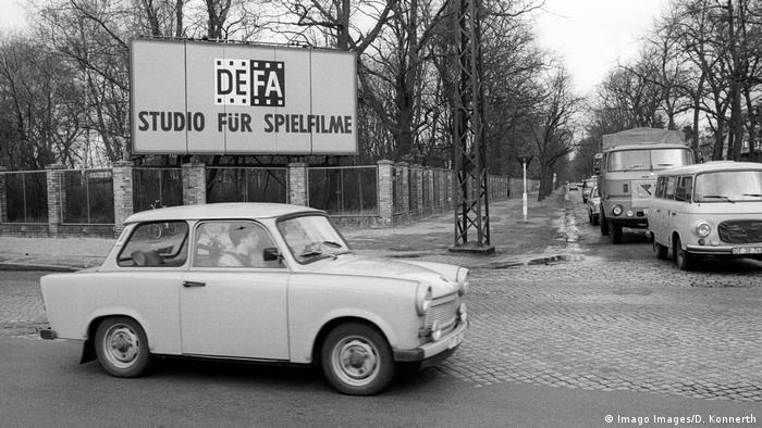 Trabant (East German car) on a city corner with a sign in the back reading DEFA: Studio for Films. DEFA Studios Babelsberg