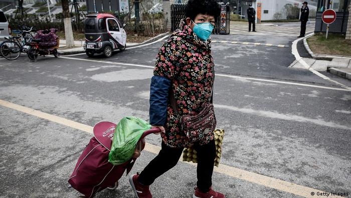 A woman wearing a face mask on an otherwise empty street in Wuhan