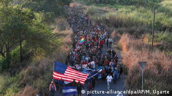 A long line of migrants marches down a road while carrying flags (picture-alliance/dpa/AP/M. Ugarte)