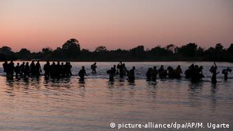 Migrants cross the Suchiate river into Mexico in early morning light