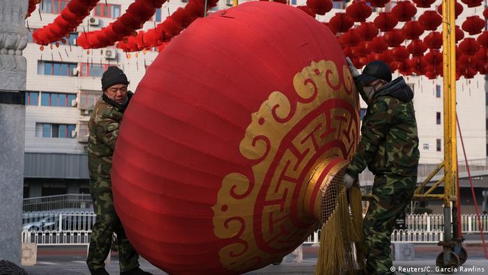 Dos soldados chinos retiran una linterna gigante mientras desmontan los adornos para la celebración del Año Nuevo Chino.