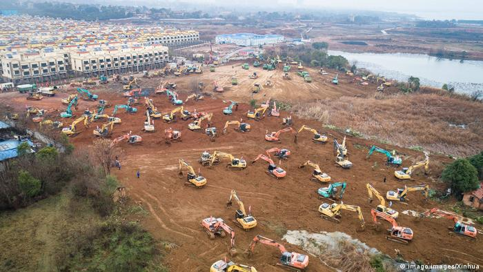 Construction vehicles and machines digging at the site of a future Wuhan hospital