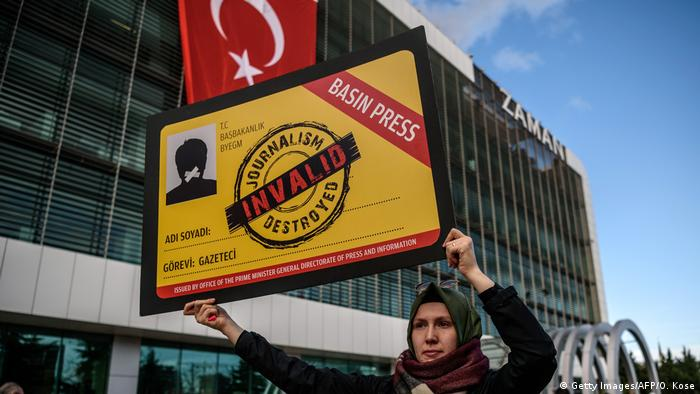 A woman holds a placard showing an invalid press card as people demonstrate in support of Turkish daily newspaper Zaman i