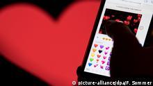 ILLUSTRATION - 12.02.2018, Hessen, Frankfurt am Main: Ein Smartphone mit Emojis aus WhatsApp vor dem WhatsApp-Logo. (Zu dpa: «Liebe in Zeiten von WhatsApp - «Schatz» ist noch immer Nummer eins» vom 13.02.2018) Foto: Fabian Sommer/dpa +++(c) dpa - Bildfunk+++ | Verwendung weltweit