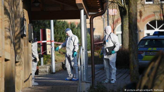 Investigators wearing white costumes